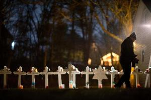 Frank Kulick walks past a display of wooden crosses and a Jewish Star of David representing the victims of the Sandy Hook Elementary School shooting on his front lawn.